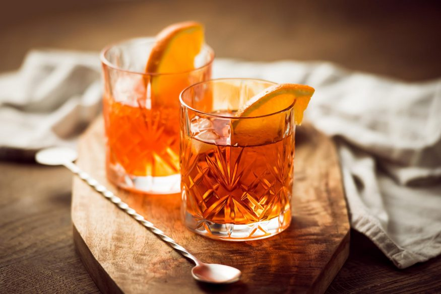 virtual happy hour: Two Scotch whisky cocktails and stirrer on top of a wooden serving board