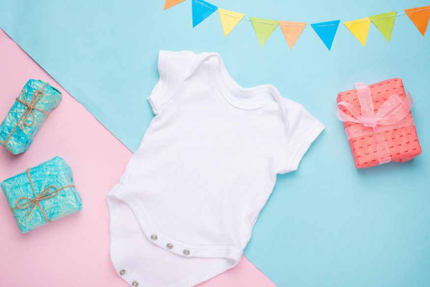 virtual baby shower games: White baby onesie surrounded by gifts and bunting
