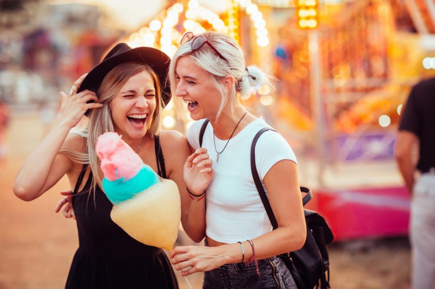 carnival theme party: Two young women laughing together in a carnival while one holds a cotton candy