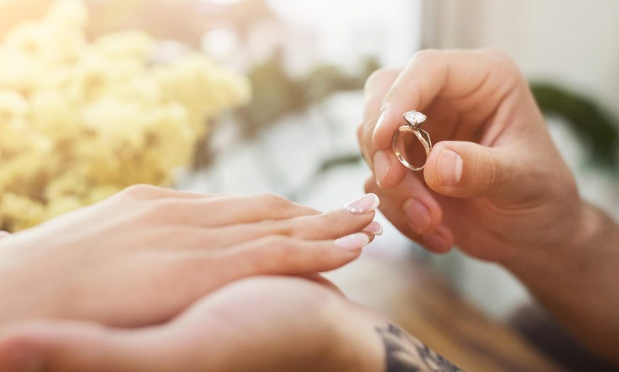 Man putting on an engagement ring on his new fiancée