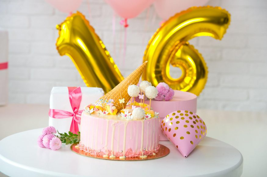 sweet 16 party ideas: Pink cake and number balloons on a table