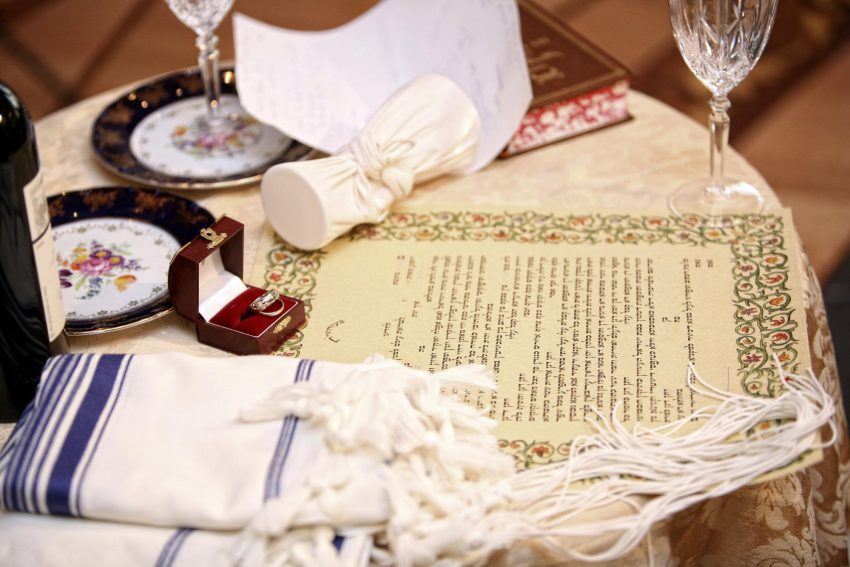Jewish wedding invitation wording: letter and a ring on a table