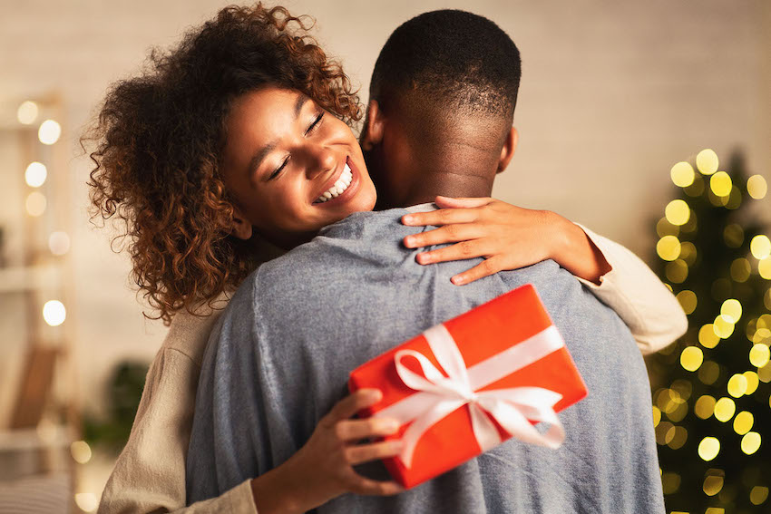 thank you card messages: woman holding a gift and hugging a man