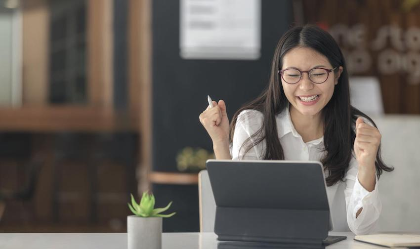congratulations on your new job: happy woman looking at her laptop