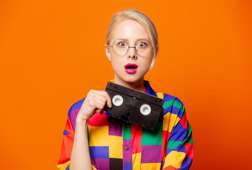 Woman wearing 90s shirt and glasses holding VHS tape