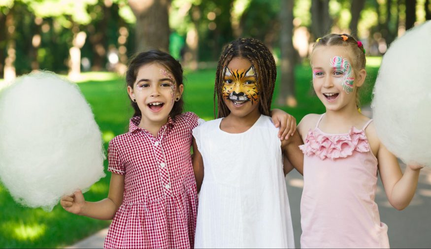 carnival theme party: Three girls smiling while holding cotton candy and face paint on
