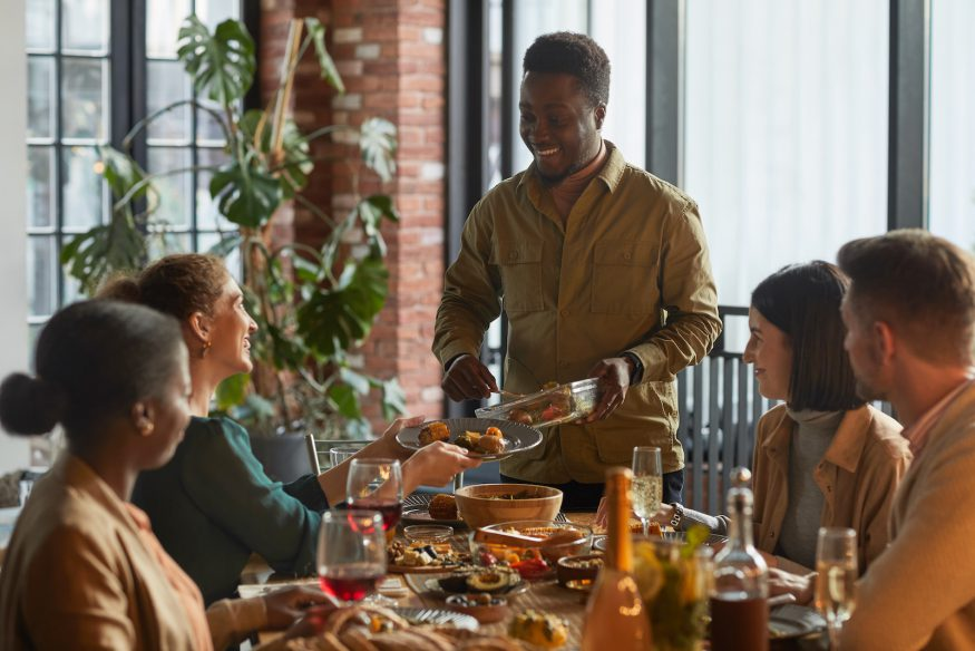 dinner party games for adults: Man serving food while hosting a dinner party for his friends