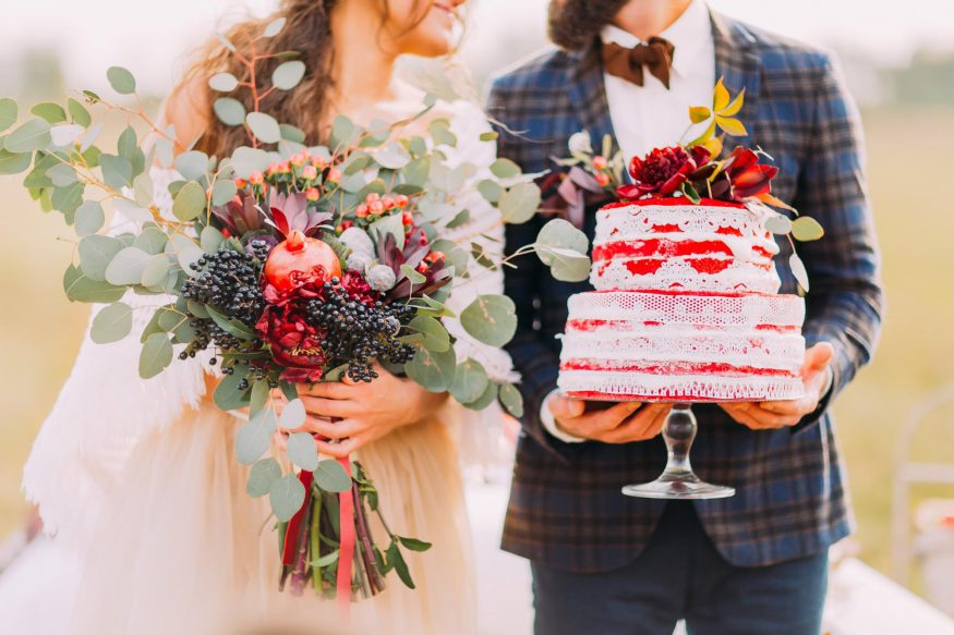 wedding on a budget: Groom holding the wedding cake and bride holding her bouquet