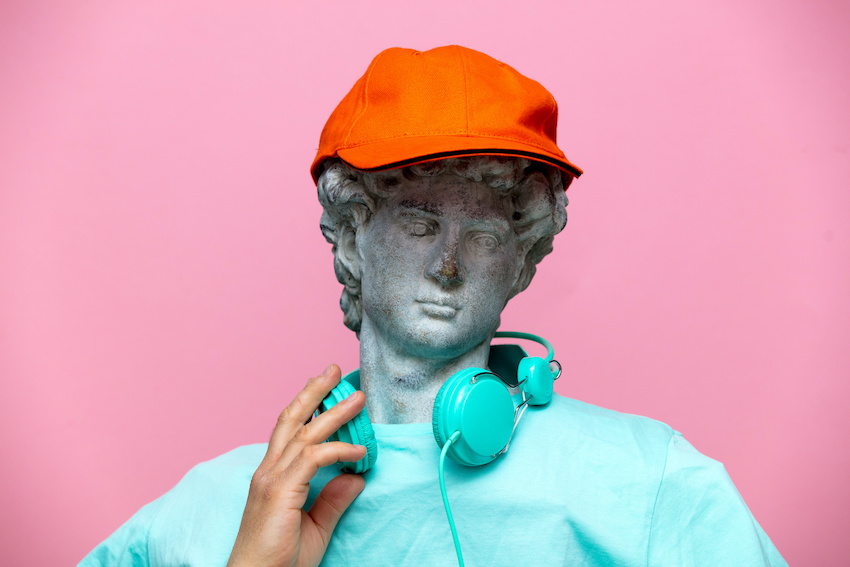 Antique bust of male in cap with headphones on pink background