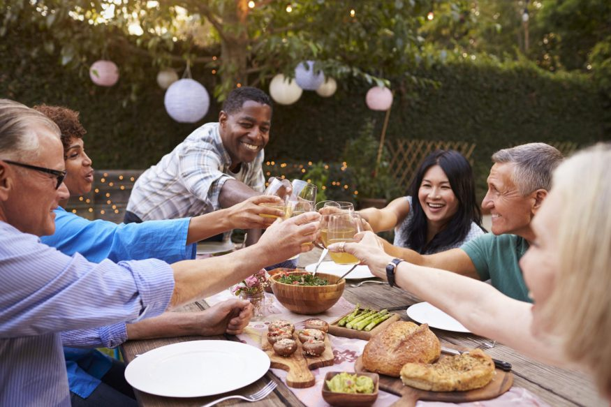 A group of friends having a toast during a backyard party