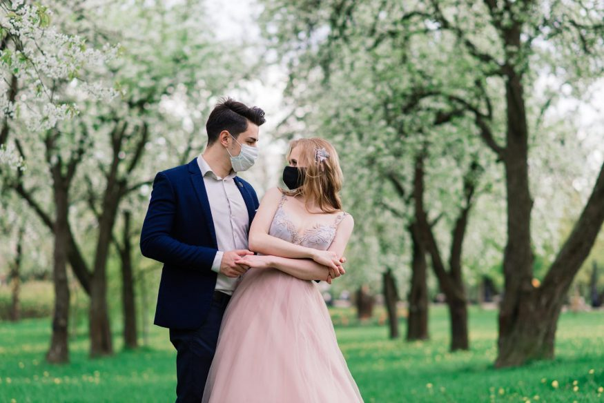 COVID wedding ideas: Wedding couple at the park while wearing masks