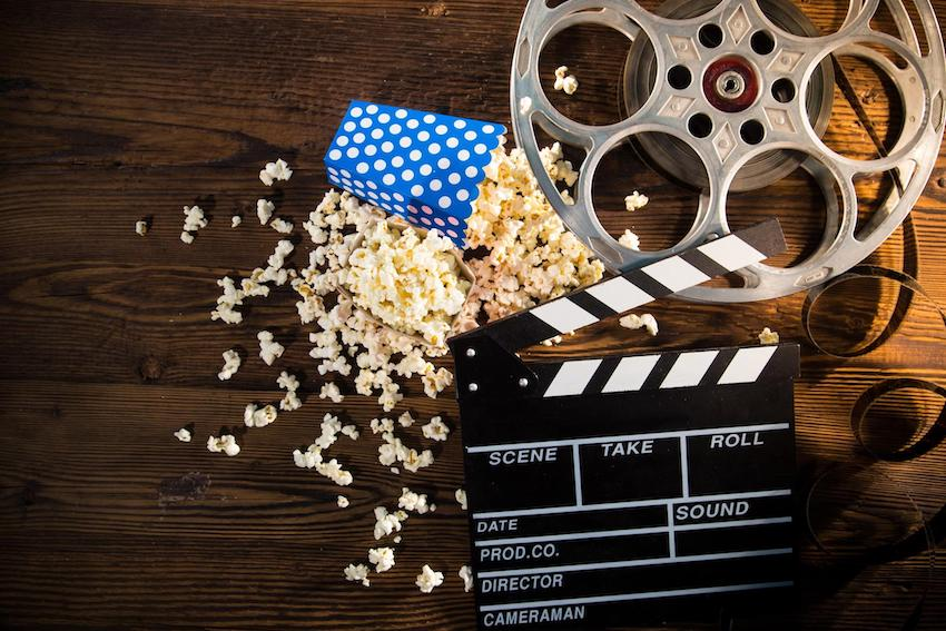 Hollywood theme party: Cinema concept of vintage film reel with popcorn