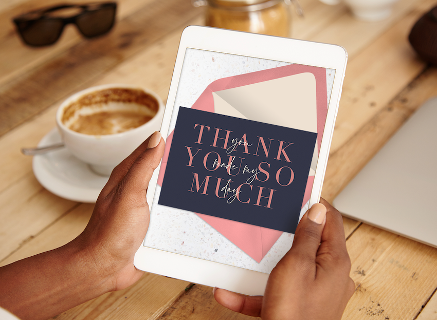 thank you card template: woman holding a tablet with a thank you card shown on the screen