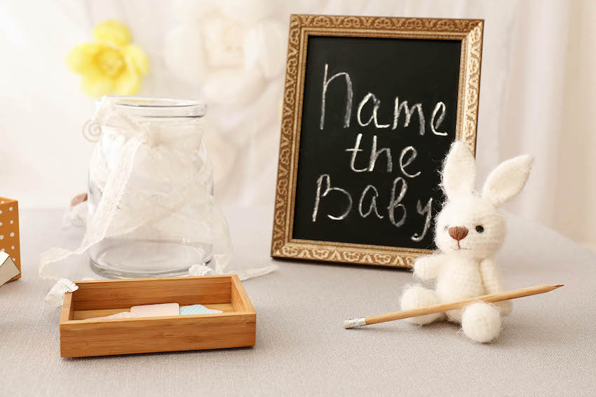 baby shower ideas for boys: Name the baby written on black frame with little rabbit