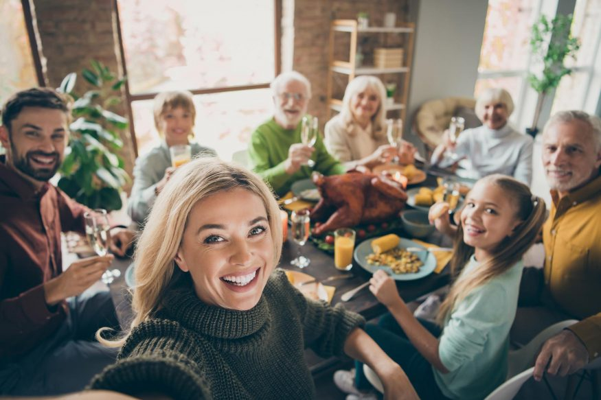 family reunion ideas: Woman taking a photo of her entire family at the dinner table