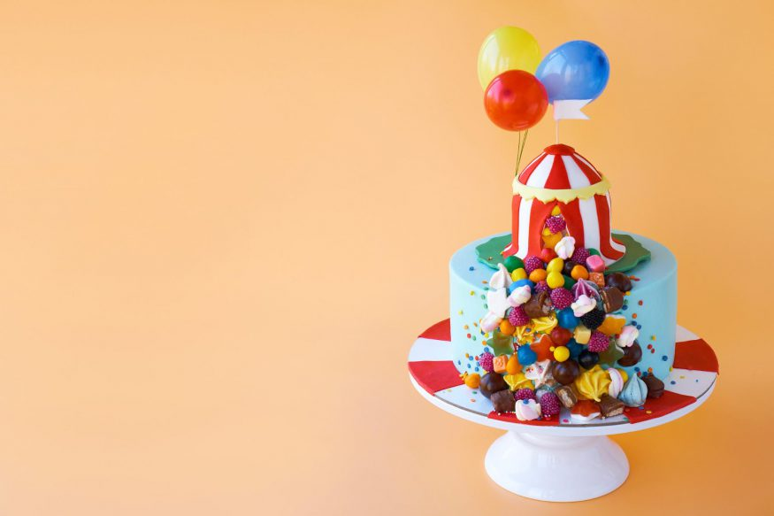 carnival theme party: Cake with circus decorations against an orange background