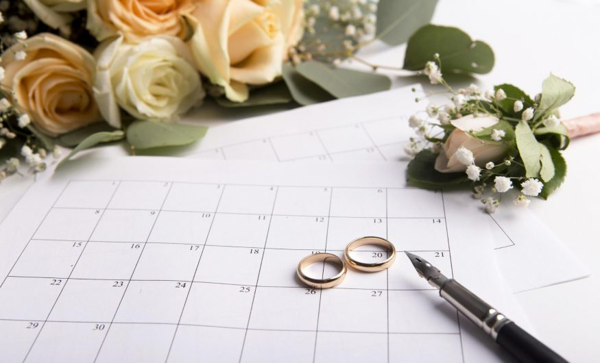 save the date postcards: Two rings on top of a calendar surrounded by flowers