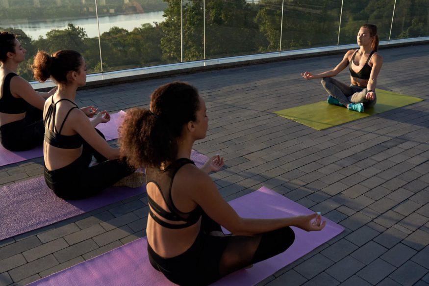 team building retreats: Group of women meditating outdoors