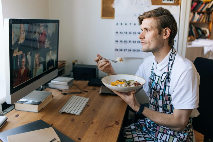 Man wearing an apron while eating in front of his computer