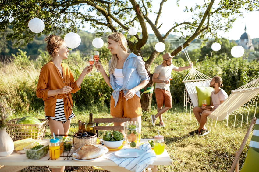 Social distancing events: Girlfriends clinking wine glasses outdoors