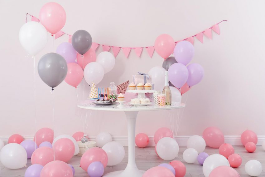 virtual baby shower invitation wording: food and drinks on a table with balloons surrounding it