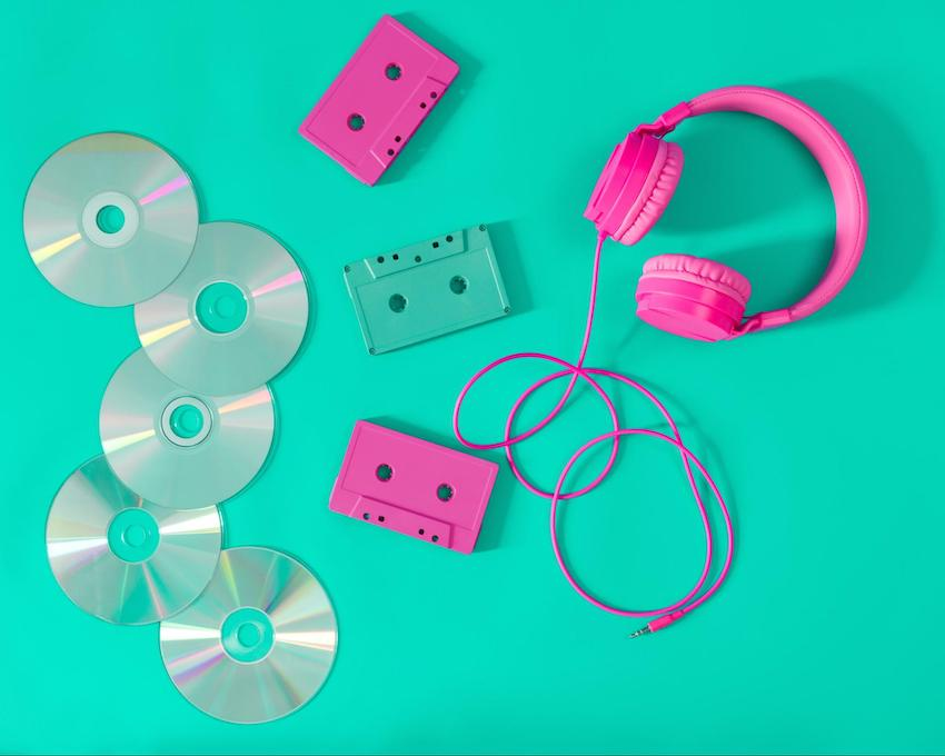 90s theme party: Pink headphones and audio cassettes with CDs