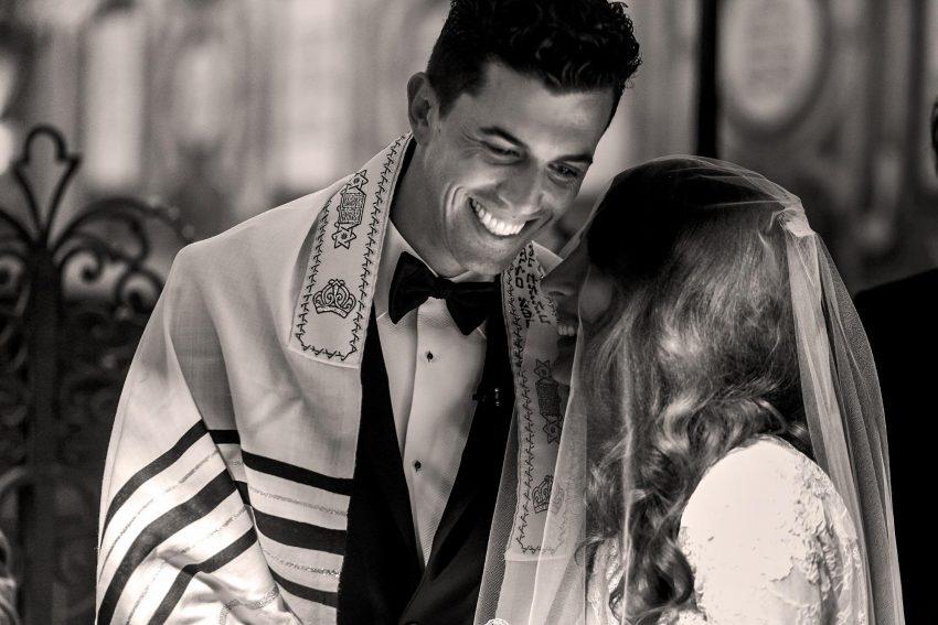 Jewish wedding invitation wording: Jewish bride and groom smiling