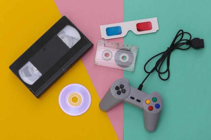 90s theme party: Wired retro gamepad, anaglyph 3D glasses, audio and video cassette, CD's on colored background