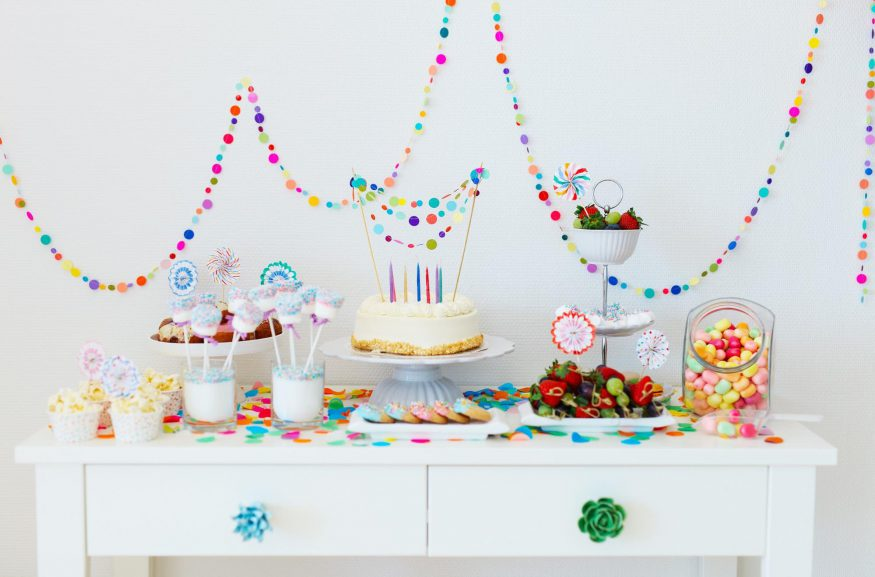 baby shower themes: Dessert table with cake, cookies, candies and colorful decorations
