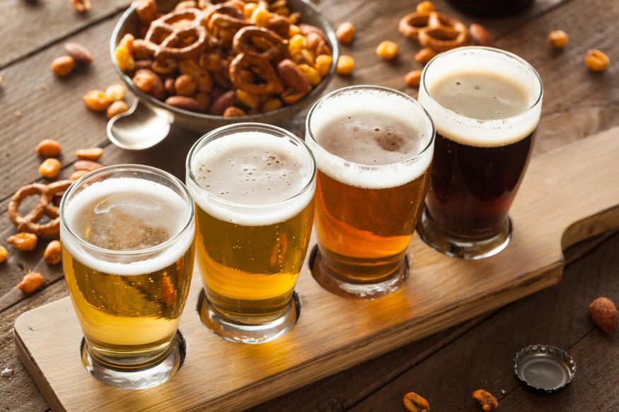 virtual happy hour: Four glasses of beer with a nuts and pretzel mix on the side