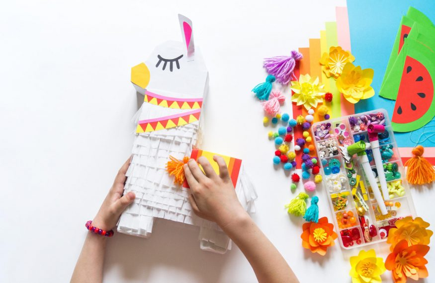 DIY party decorations: Person decorating a piñata on top of a white surface with decorating tools on the side