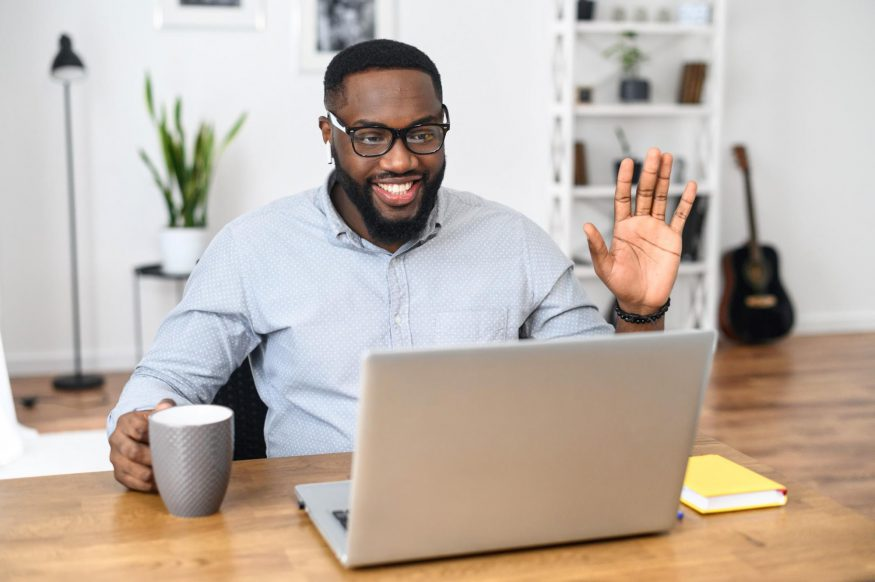remote team building activities: Man smiling and waving in front of his laptop
