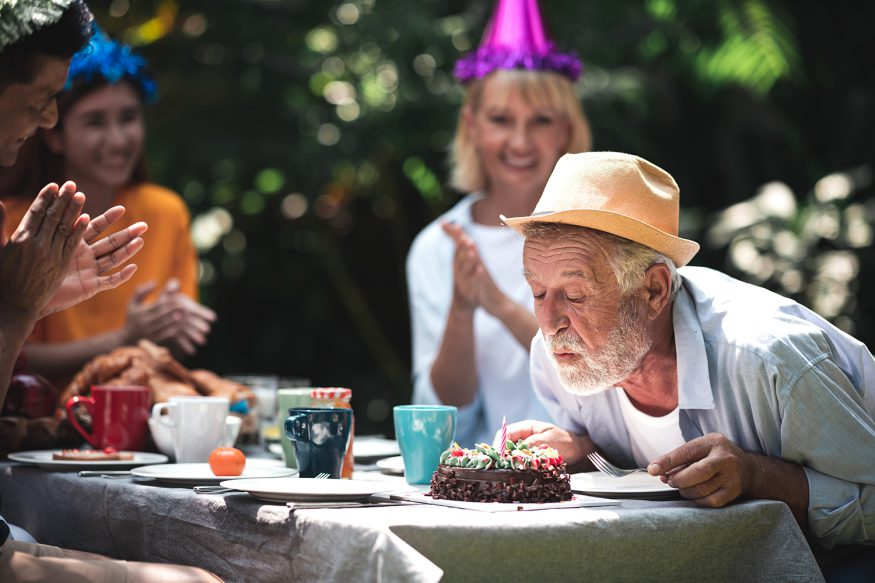 Old man blowing his birthday cake