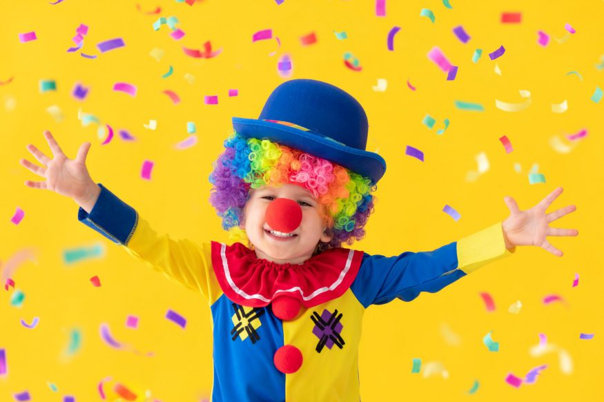 carnival theme party: Child in clown costume against a yellow background with confetti floating around