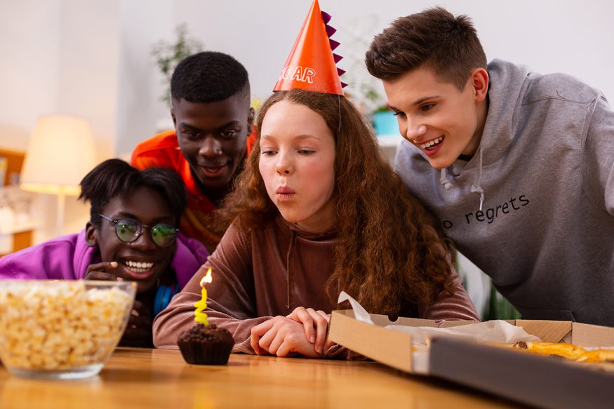 teen birthday party ideas: girl blowing out candle while surrounded by friends at a party