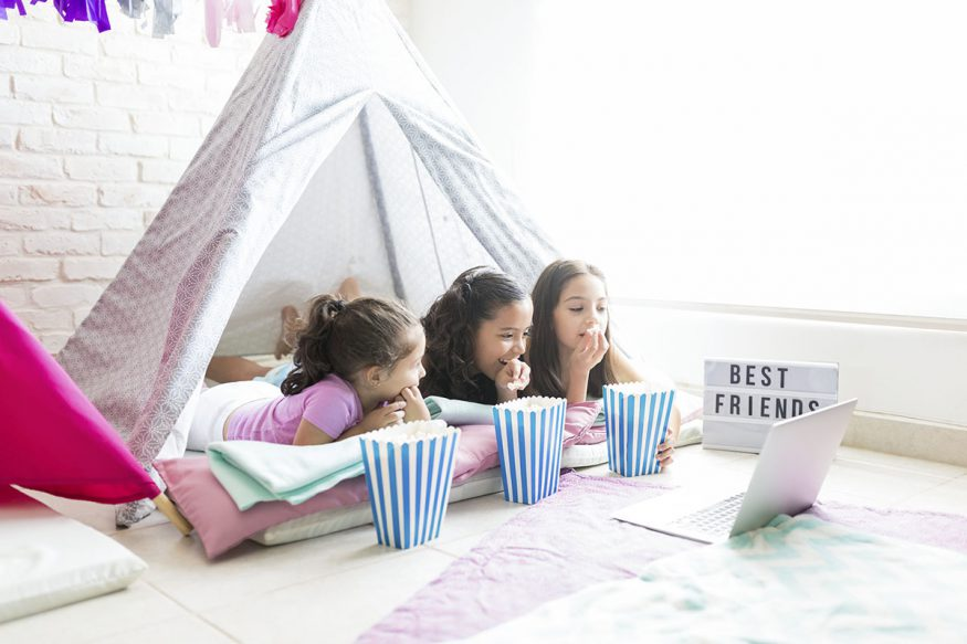 sleepover invitations: kids eating popcorn while watching a film in their tent