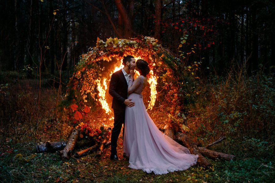 fall wedding decorations: couple kissing at an outdoor night wedding ceremony