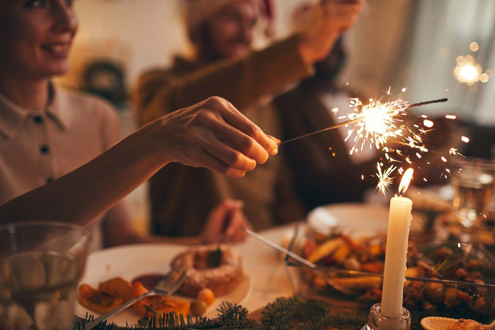 Woman lighting a sparkler at the dinner table