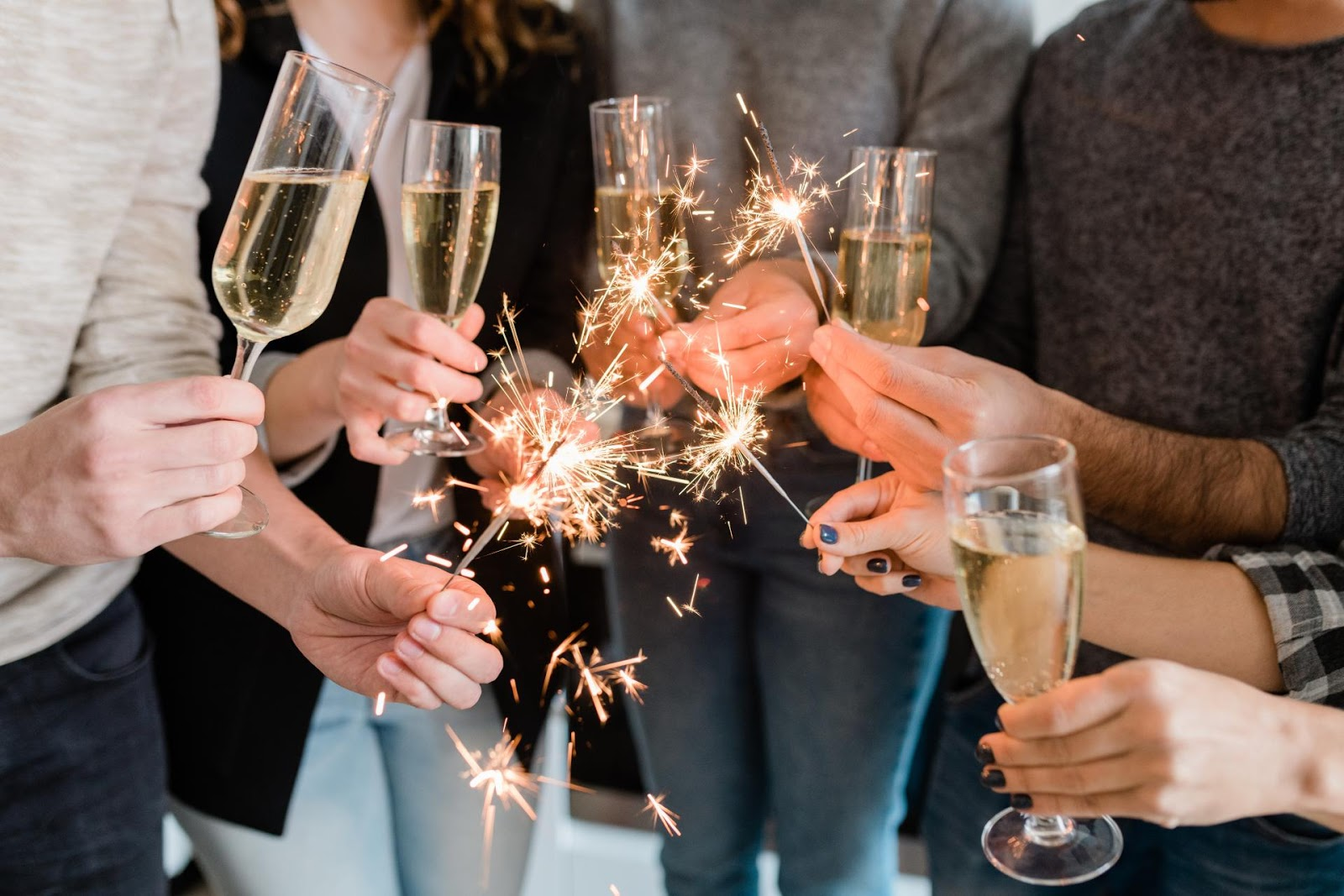 Partygoers holding champagne flutes and sparklers