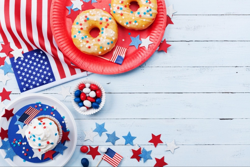 Sweet snacks surrounded by flags and stars on a white wooden surface