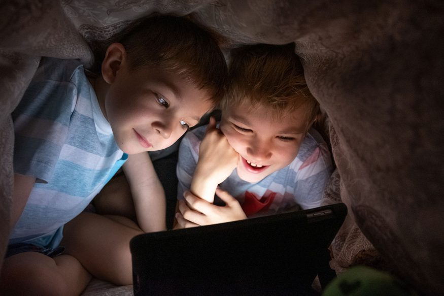 two boys watching a movie on a tablet
