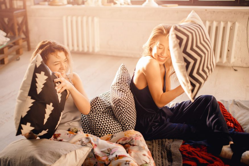 slumber party ideas: two women sitting on the floor while holding a pillow