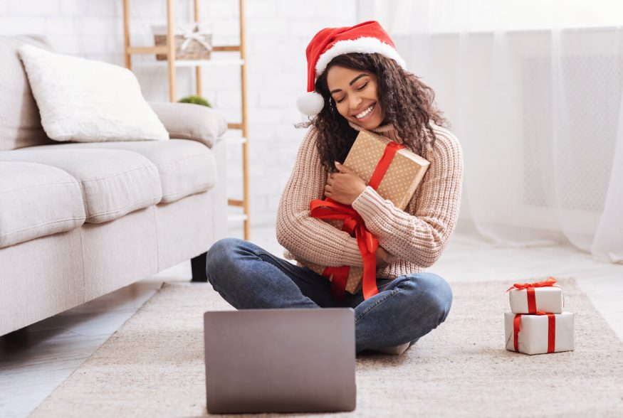 Virtual Christmas party ideas: woman hugging her gift while on a video call