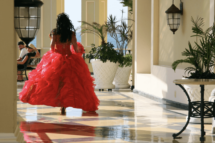 quinceanera gifts: Woman in red gown walking in the hallway